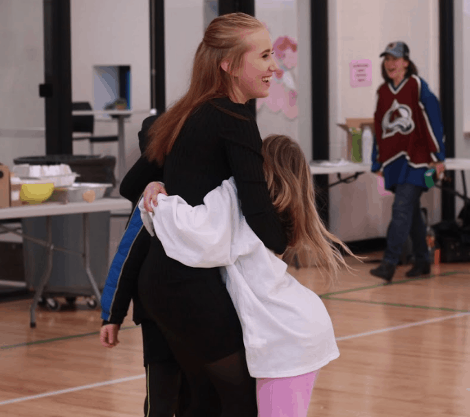 Young girl from Finland is hugged by children at an elementary school volunteering abroad